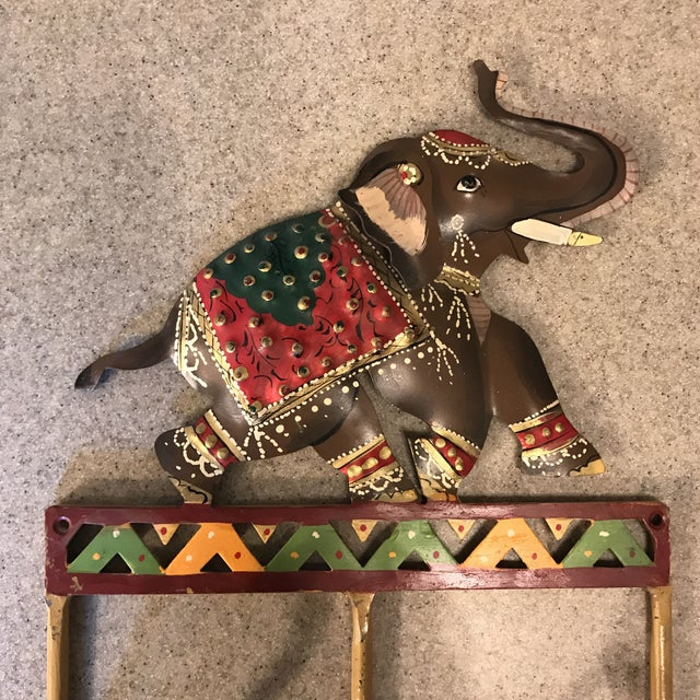 "Beautiful and quirky elephant coat hook! Hand painted metal with 3 hooks. Measures 8"" wide x 10.5"" tall. Hooks project 2.5"""
