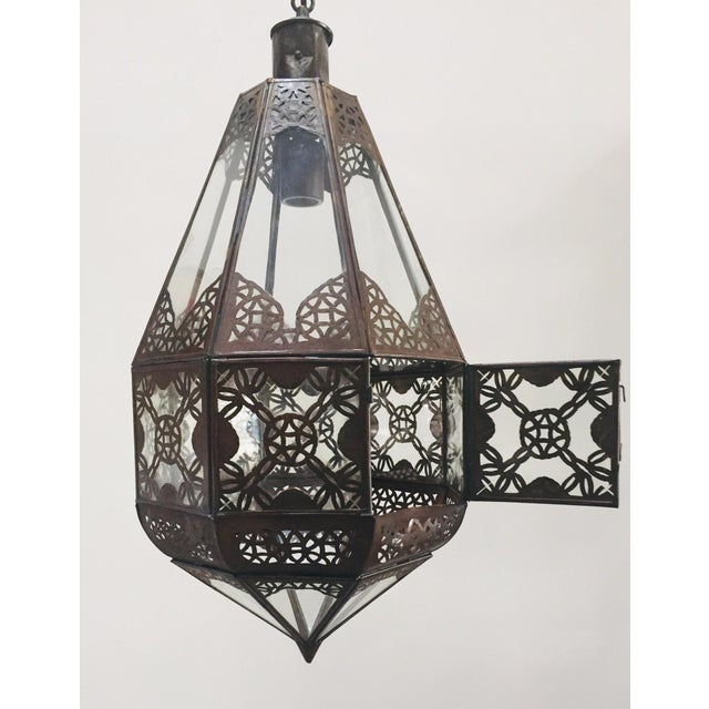 Stylish handcrafted Moroccan lantern in clear glass. Antique bronze rust finish metal with Moorish filigree designs. This...