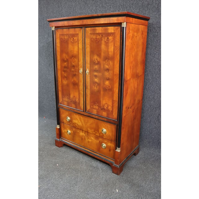 French Empire style armoire by Century Furniture. Made of cherry and Burl wood , black ebonized trim , 2 doors with fitted...