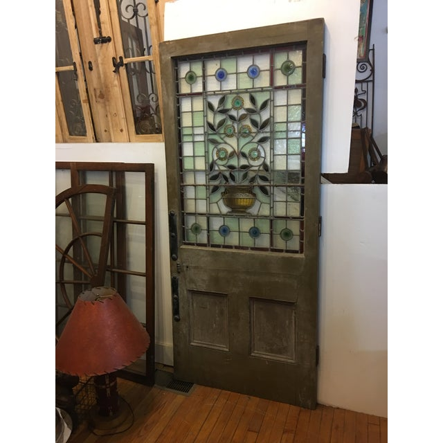 A very beautiful old 1920's English stained glass door. Wonderful floral urn design with jewels. Great colors. In good...