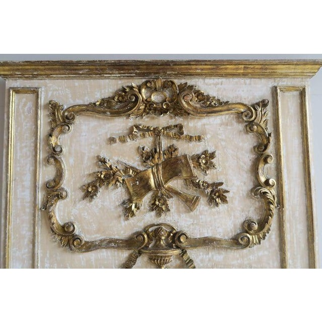 French Louis XV style painted and parcel-gilt mirror depicting musical instruments combined with urns and flowers...