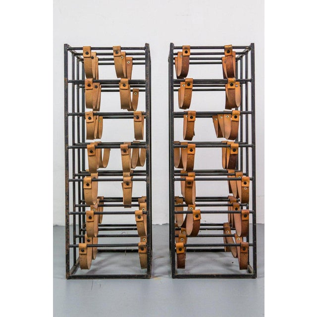 Pair of wine racks designed by Arthur Umanoff, made of wrought iron with leather straps. Solid iron frame with three...
