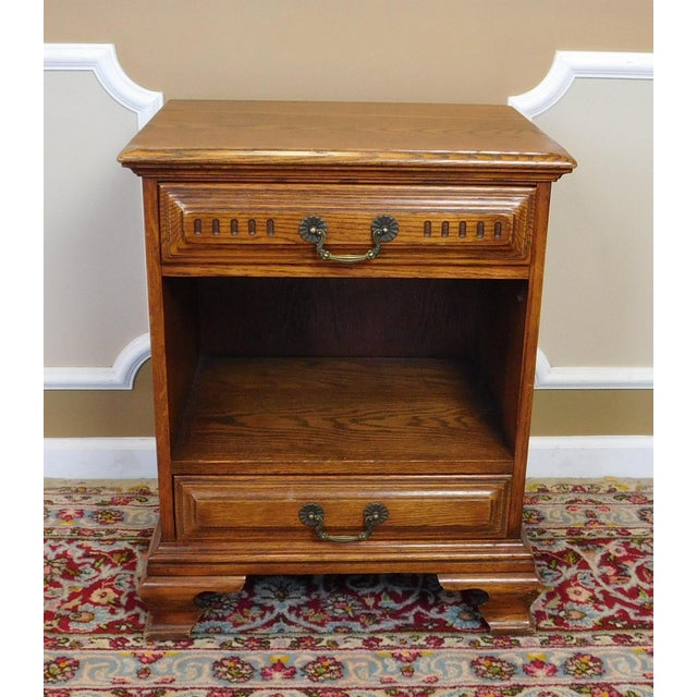 This is a very good quality solid oak bedroom night table stand made by The Davis Cabinet Company, circa 1970s. Squared...