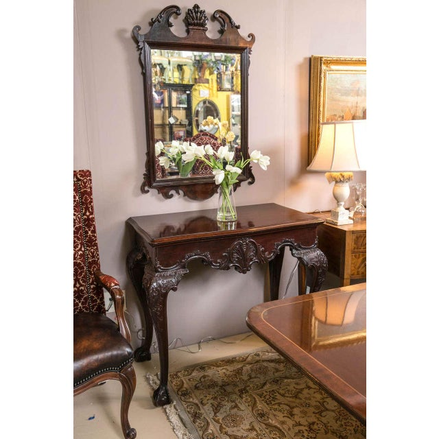 Handsome pair of English Georgian style mahogany side or console tables. Each having a molded serpentine top above a...