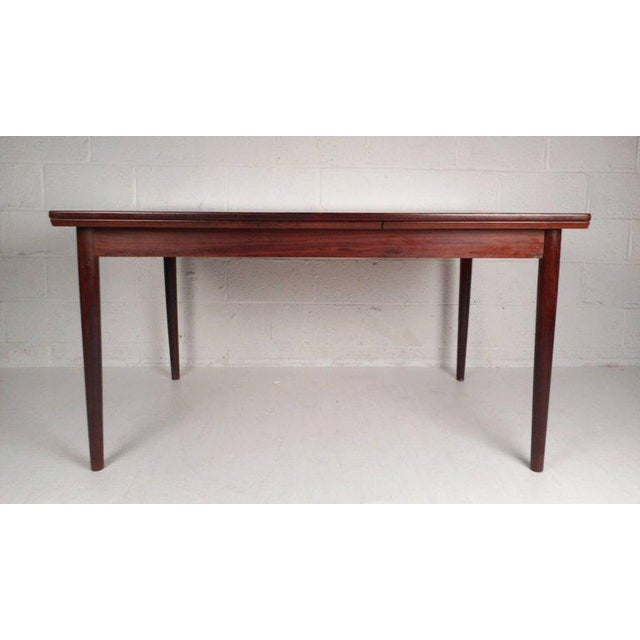 This beautiful vintage modern dining table features the ability to extend all the way to 97.5 inches wide from the...