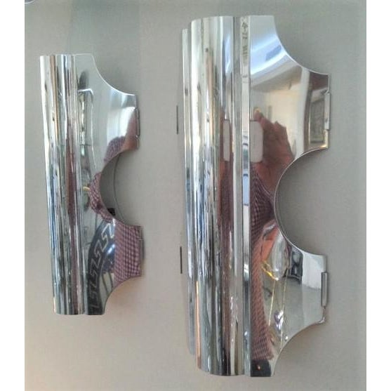 This stylish and mod pair of polished aluminum wall sconces date to the 1960-1970s and were created by the Doria Leuchten...