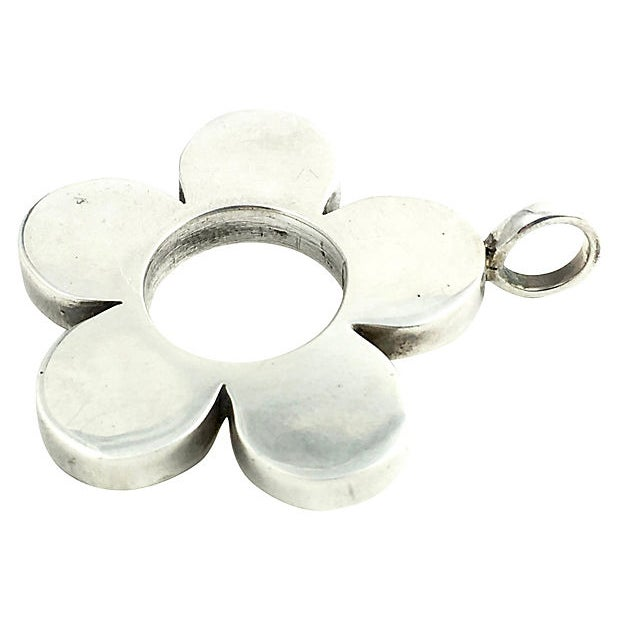 "Sterling silver open flower pendant. Marked ""925"" on edge of bottom petal. Age wear, light scratches."
