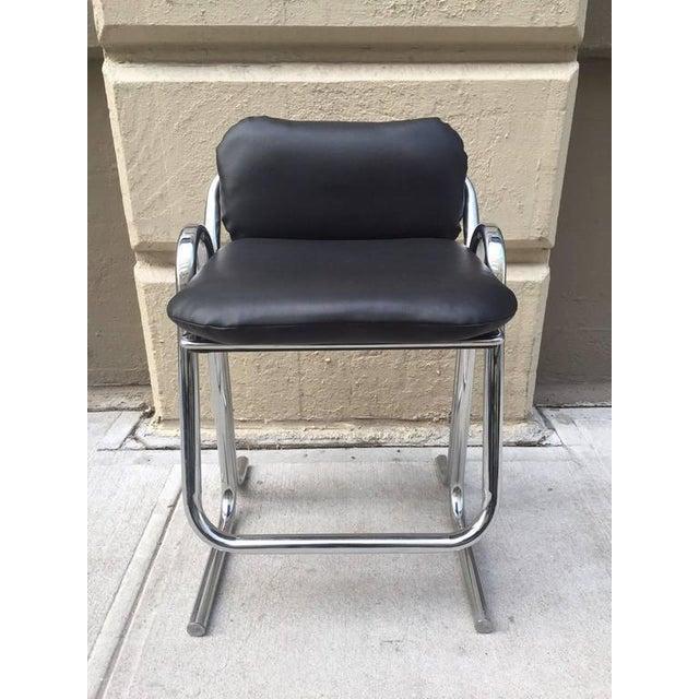 Set of four vintage stools by Jerry Johnson. Black vinyl seats and backs with tubular chrome frame.