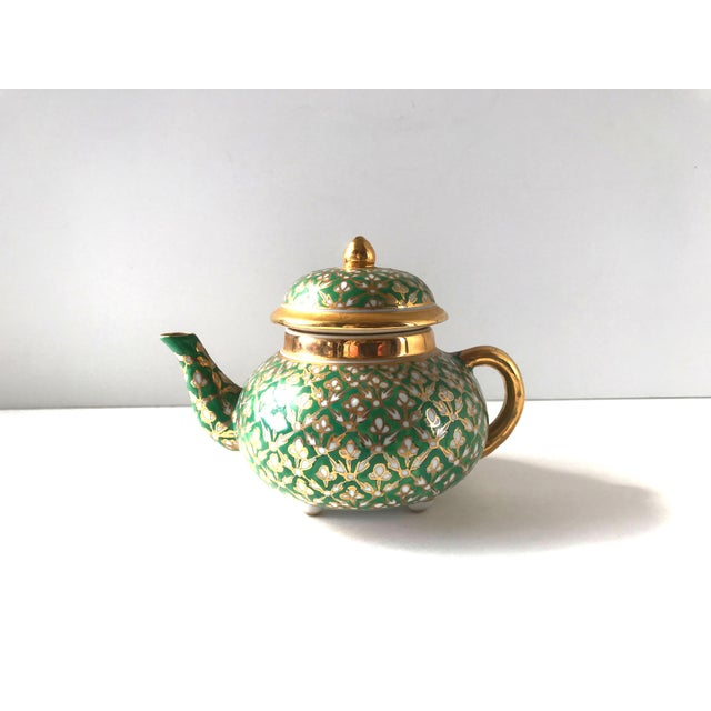 An antique, Old Paris Porcelain small footed teapot of porcelain, hand-painted with an ornate, hand-painted design of gold...