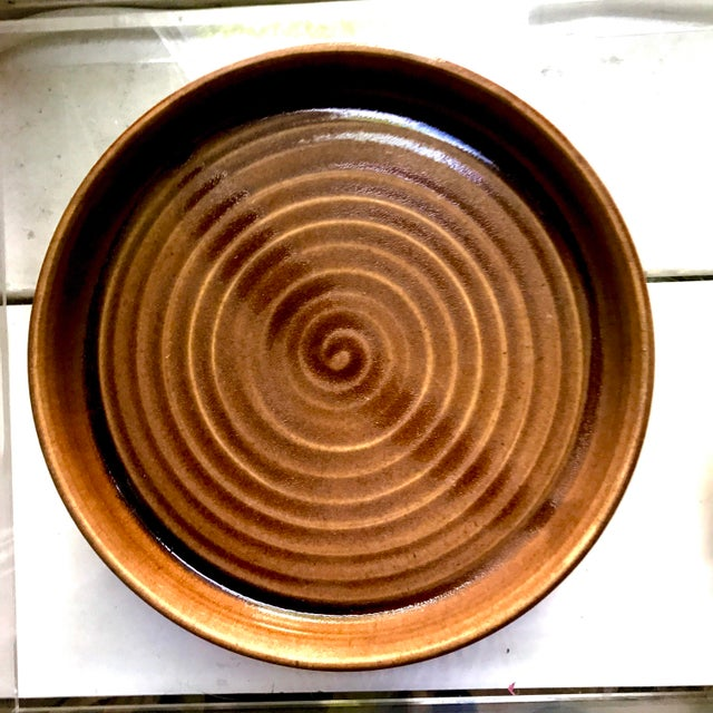 Hand formed round studio pottery platter with rim. This beautiful piece is covered in a thick brown glaze with dripping...