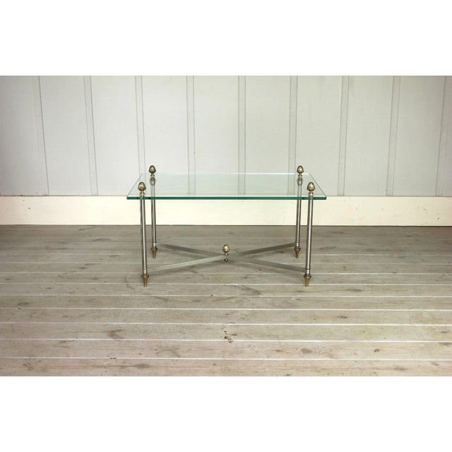 Very stunning brass, brushed metal and glass coffee table in the style of Maison Jansen. It's in very good vintage...