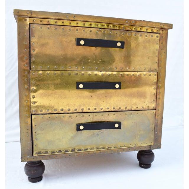 Sarreid brass 3-drawer chest with leather & brass pulls. 3-drawer brass chest with tack details and ebonized wood feet.
