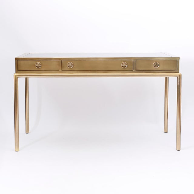 Midcentury three-drawer writing desk with a leather top, stylized Campaign hardware, sleek elegant form, and a chic custom...