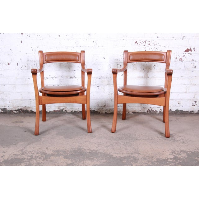 An outstanding pair of sculpted solid teak studio craft club chairs. The chairs feature unique sculpted teak frames with...