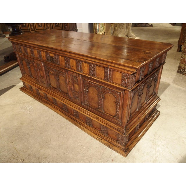 This elegant 18th Century walnut wood Italian trunk is in the Early Renaissance Style. It's predominant motif is multiple...