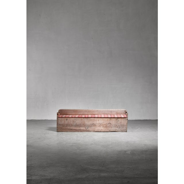 A 19th century folk art bench in pine from Sweden. The bench has an upholstered seat that can be flipped open to reach a...