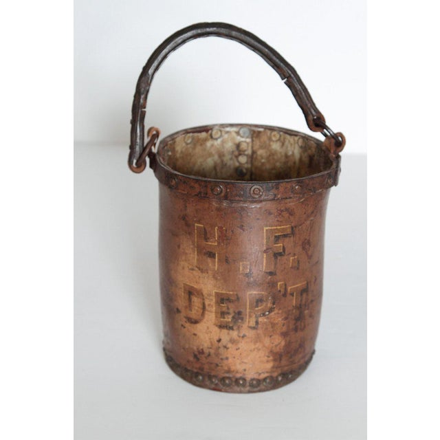 A mid 19th century leather fire bucket. A metal ring around the top of the bucket is affixed by metal tacking and...