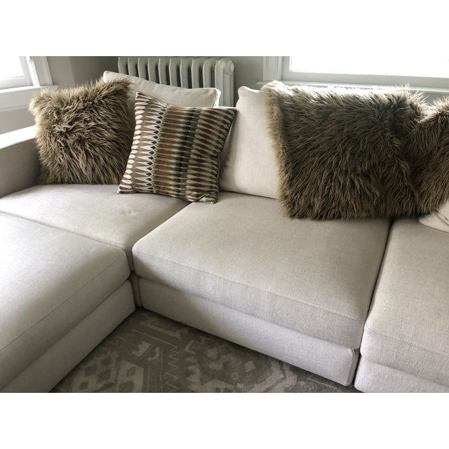 A super slinky very large low sectional sofa having 3 loose seat and back cushions and roomy complimentary ottoman that...