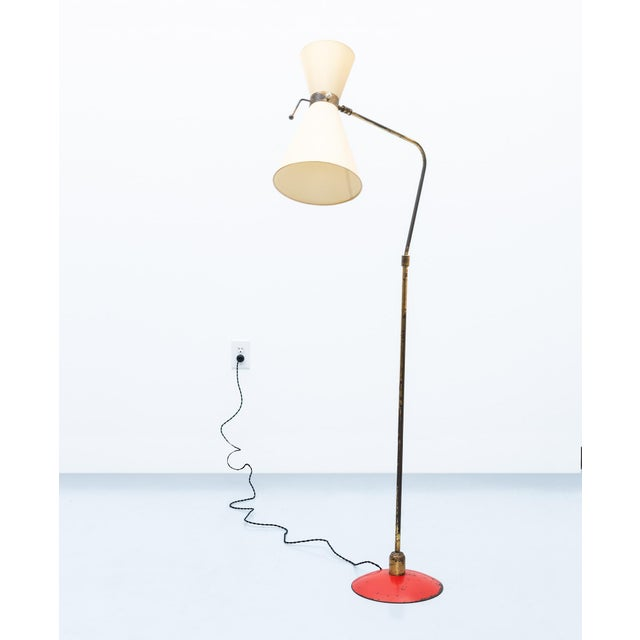 An Italian floor lamp in brass with heavy, red lacquered metal base. Original diabolo shade in linen fabric. Articulating...