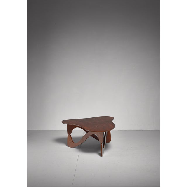 A plywood, freeform coffee table with helix shaped legs, by Brazilian designer José Zanine Caldas. Labeled underneath.