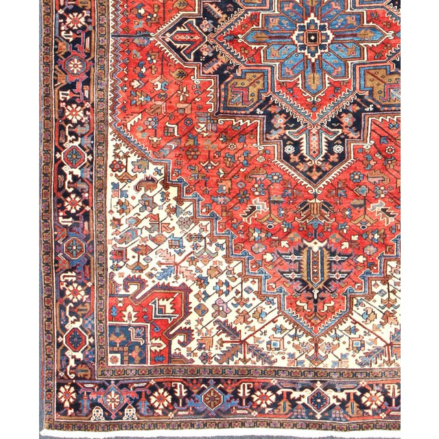 Hand-knotted Semi Antique Heriz rug with medallion design in red, ivory, and multi-colors. The piece is from the 1930s....