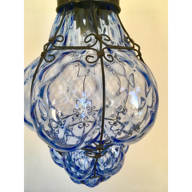 Wow, what a gorgeous shade of blue! This caged blue glass pendant truly pops and can work in a number of rooms. It's hard...