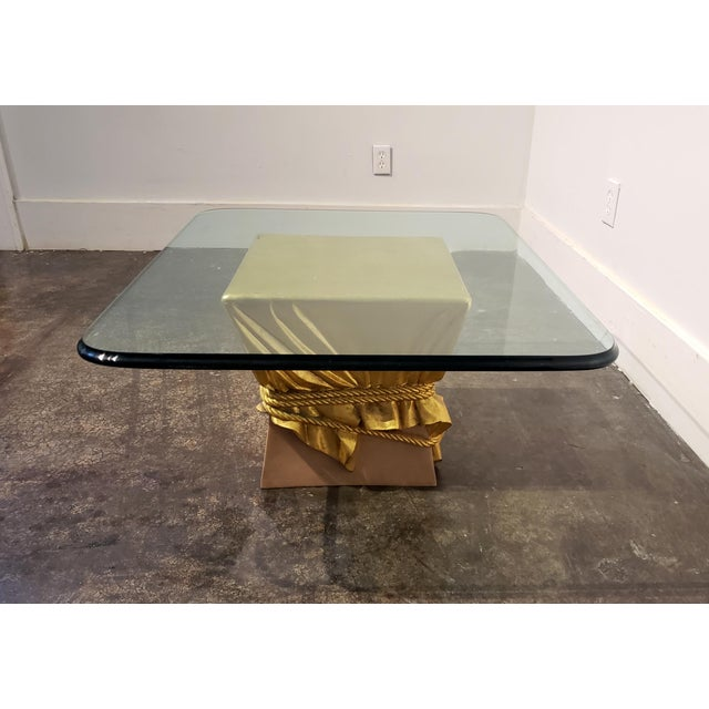 Coffee table with gold-leafed sculpted drapery and ropes seemingly squeezing a pink package. Painted and sculpted wood and...