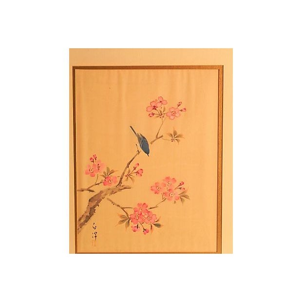 A charming image painted on silk, depicting a blue bird among delicate pink cherry blossoms. The silk print is matted and...