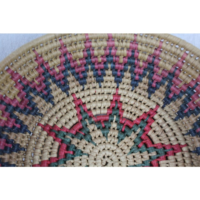 Handwoven grass swirled African tribal basket with starburst design in tan, pink, blue, red, and green. Made in the mid...