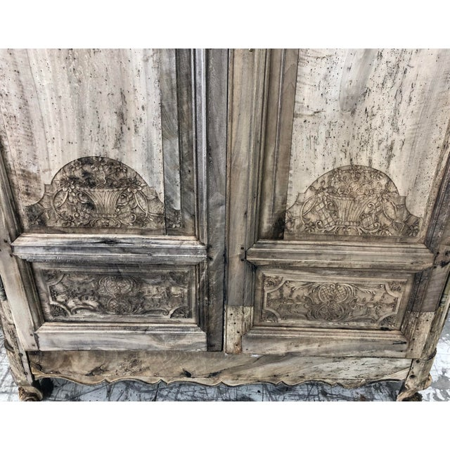 French Renaissance Bleached Oak Armoire. Consisting of a rounded corner crown, above two carved figural arched doors with...