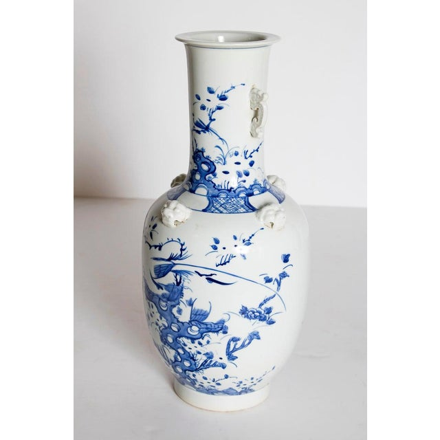 """A tall (17"""") Chinese blue and white porcelain vase. This unique baluster form vase has white applied handles on the neck..."""
