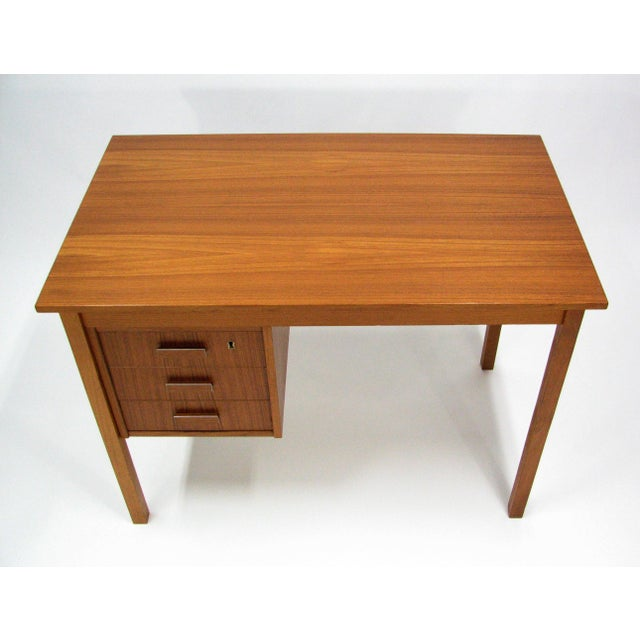 A strikingly handsome teak writing desk by Ejsing Møbelfabrik A/S. Three locking drawers with aluminium trim pulls and the...