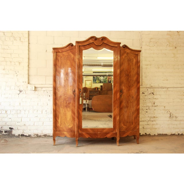 This is an amazing 1870 burled and inlaid French Knockdown Wardrobe with beveled mirror. It has intricate inlaid details...