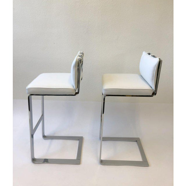 A beautiful polish chrome and white leather pair of barstool design in the 1970s by Milo Baughman. Newly reupholstered in...