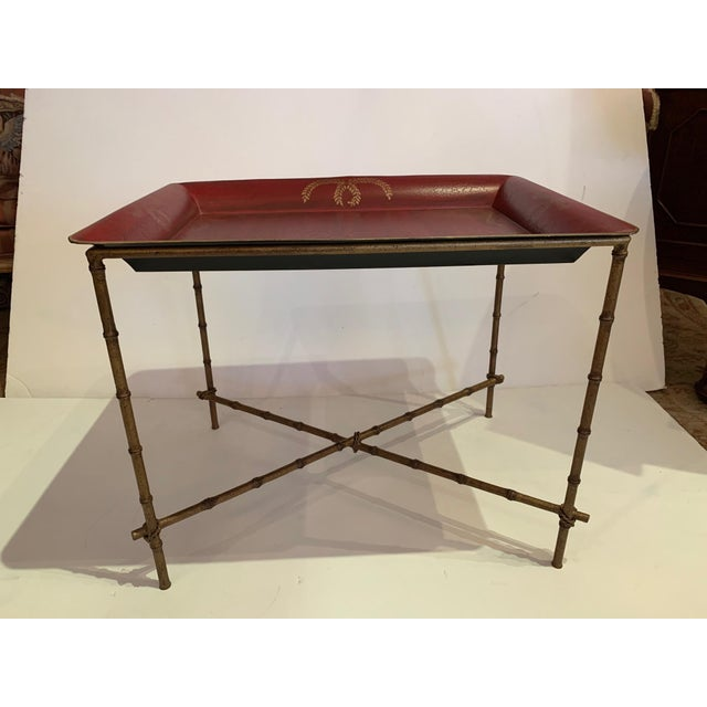 Stunning tray top end table with a rich pop of color having red top adorned with gold and elegant faux gilt bamboo base.