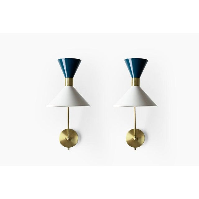 Monarch is a large scale wall-mount reading lamp or sconce with articulated arms. The wide brass band and dramatically...