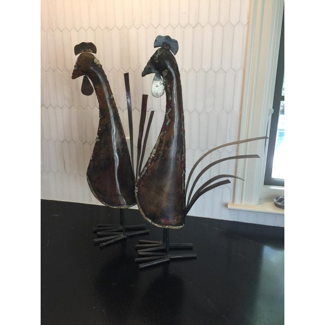 I purchased this pair of roosters in Auckland, New Zealand about 25 years ago from a local artist. They are made of metal...