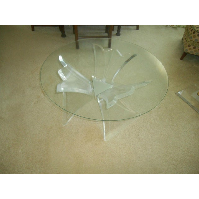 Gorgeous Mid-Century Modern clear lucite floral base & glass top cocktail table. The cocktail table starts with a three...