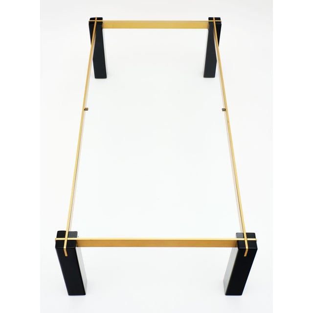 A rectangular French modernist brass and black coffee table with square section legs and clear glass, inserted on the top...