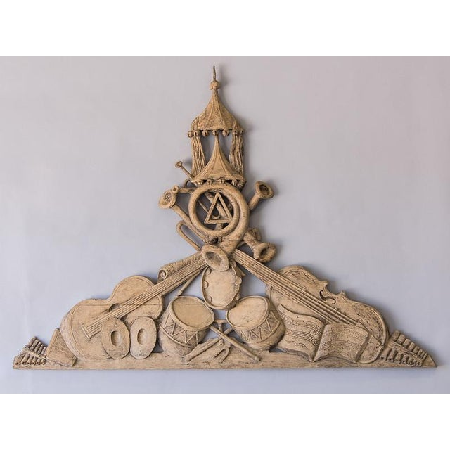This triangular shaped sculptural depiction of various instruments arranged to showcase their individual nature is...