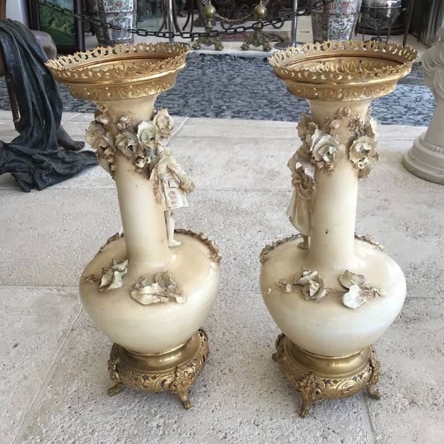 Pair of old Paris porcelain hand painted vases. The body is made of porcelain with a gilded gold bronze base & crown. Each...