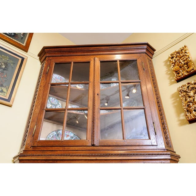 Carved oak corner cabinet with paneled doors in the bottom and astragal doors above. The glass is original and the cabinet...