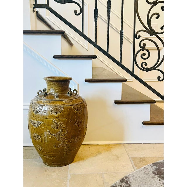 Heavily potted in a robust baluster form, this Chinese stoneware storage jar is covered with a thick yellow glaze. With a...