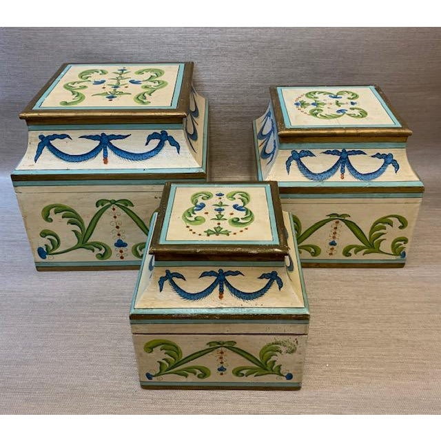 Pretty set of 3 painted boxes with brass hinges and curved profile. Painted leaves and swags decorate each side. Largest...