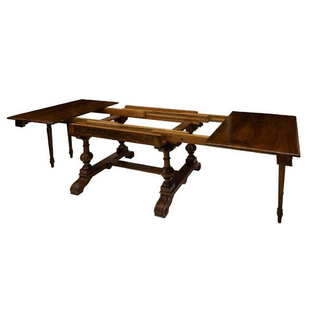 This antique Italian walnut extension dining table was built in the 19th c. The rectangular top over apron with floral...