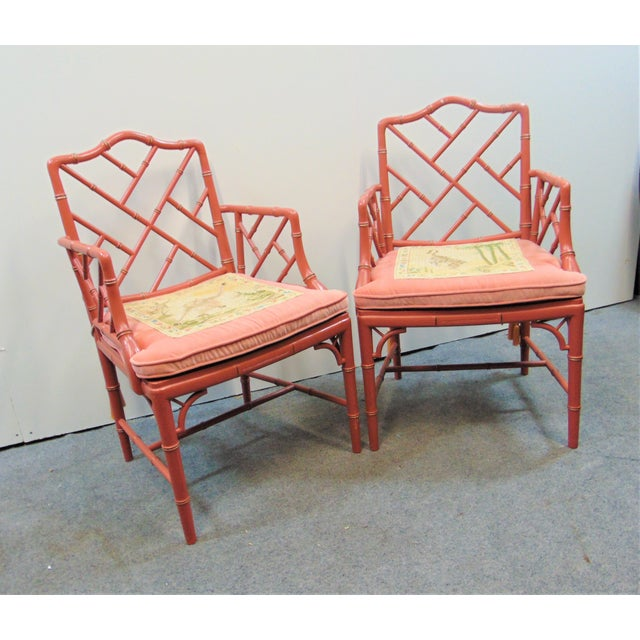 A pair of regency style faux bamboo arm chairs, rose painted finish with gold highlights, loose cushion seat with caning...