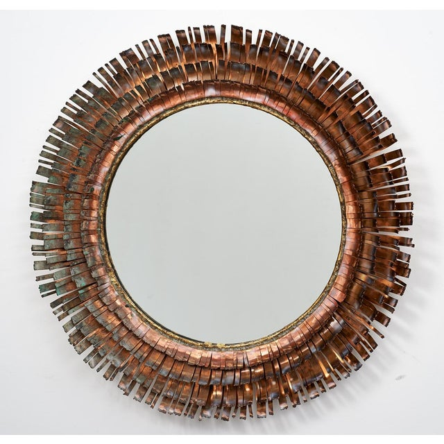 An iconic Brutalist focal point mirror in torch cut and hammered brass and copper. Composed of four concentric rings of...
