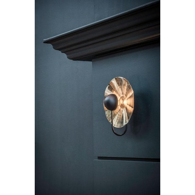 A satin copper wall light with a satin black covered light which reflects warm LED light back from a faceted copper...