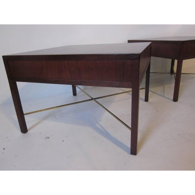 A pair of dark Brazilian rosewood end tables with the satin brushed brass X-stretcher bases.