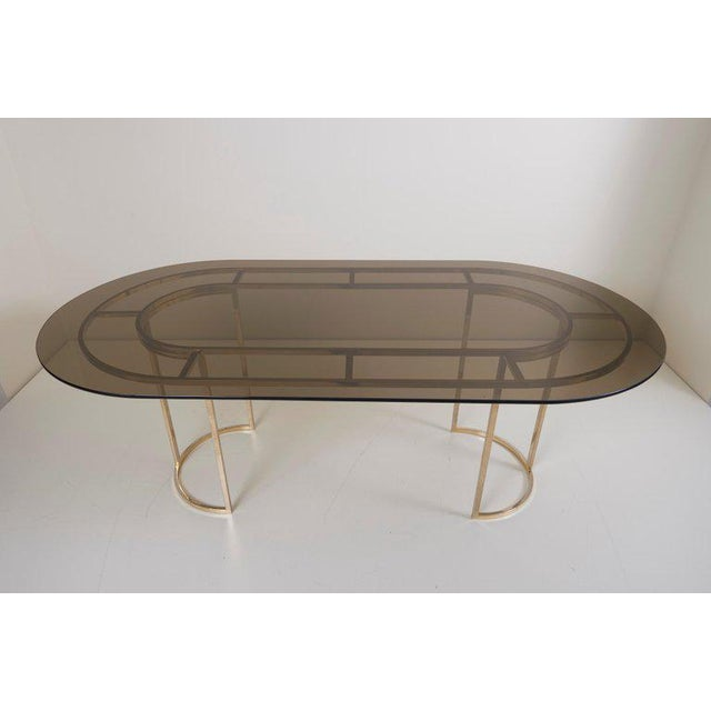 Beautiful large dining table in brass with a tinted glass table top by Romeo Rega. The table is in a very good condition....